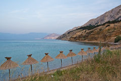Parasol on the coast of Krk , Croatia Royalty Free Stock Image