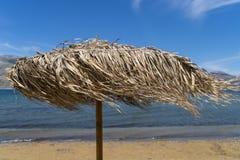 Parasol, día ventoso en la playa fotografía de archivo