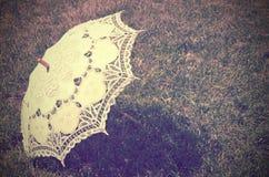Parasol de encaje en la hierba vintage teñido Fotos de archivo libres de regalías