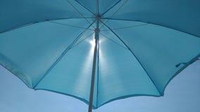 Parasol de playa con el sol detrás de él fotos de archivo