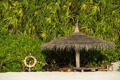 Parasol de playa hecho de las hojas de palma en el fondo de un exótico Foto de archivo libre de regalías