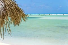 Parasol de playa hecho de las hojas de palma en la playa exótica Fotos de archivo libres de regalías
