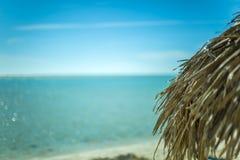Parasol de playa hecho de las hojas de palma en la playa exótica foto de archivo libre de regalías