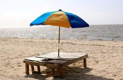 Parasol de playa multicolor en soporte de madera en la playa Imagenes de archivo