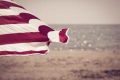 Parasol de playa rayado brillante como fondo del verano Imagenes de archivo