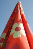 Parasol de playa rojo doblado Fotos de archivo