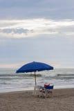 Parasol de playa y sillas al lado del mar Imagenes de archivo