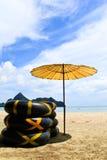 Parasol en ring op het strand Stock Afbeeldingen
