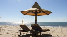 Parasol en twee sunbeds op het strand Stock Fotografie