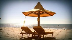 Parasol en twee sunbeds op het strand Stock Foto's