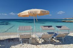 Parasol and loungers on the beach. Three loungers and yellow parasol on the white sand beach stock photography