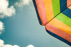 Parasol. A multi.colored parasol in front of a blue, cloudy sky Royalty Free Stock Images