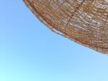 A parasol near the sea. Blue sky. At the beach. View from a deckchair Stock Photos