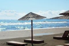 Parasol od słońca robić płochy i drewniany sunbeds stojak puści na plaży, iskrzasty morze z fala Fotografia Stock