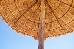Parasol op het strand door het overzees Stock Foto