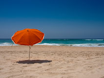 Parasol orange sur la plage Photographie stock libre de droits