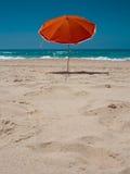 Parasol orange sur la plage Images libres de droits