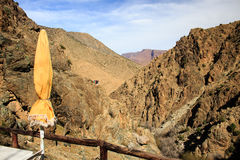 Parasol and  Panoramic View of Atlas mountains in Morocco. Yellow parasol in canyon in the High Atlas mountains near Setti Fatma in Ourika Valley Royalty Free Stock Image