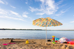 Parasol on river bank, under which the scattered items and toys Royalty Free Stock Image