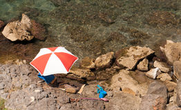 Parasol on the rocks in front of the sea Royalty Free Stock Photography