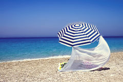 Parasol on sandy beach Stock Images