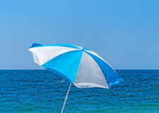 Parasol on the shore Stock Photos