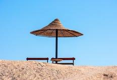 Parasol simple du soleil et banc de places assises contre un ciel bleu images stock