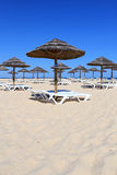 Parasol and sun loungers on Algarve beach. Parasol and sun loungers on the beach sand, Tavira island, Algarve. Portugal stock image