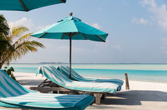Parasol and sunbeds by sea on maldives beach Royalty Free Stock Photos