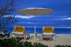 A parasol and two beach beds Royalty Free Stock Images
