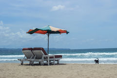 Parasol umbrella and chairs on beach with ocean behind Royalty Free Stock Photography