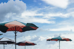 Parasol umbrellas on beach with cloudy sky behind Stock Image