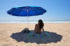 Parasol with woman sit on towel Royalty Free Stock Image