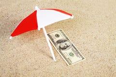 Parasole del unter della banconota in dollari dell'americano cento dei soldi sulla sabbia della spiaggia Immagini Stock