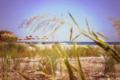 Parasole i bryczka hole na plaży błękitny skał denny seascape nieba lato Zdjęcie Stock