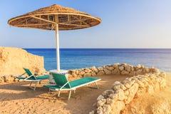 Parasole i dwa pustego deckchairs na brzeg piasku wyrzucać na brzeg Fotografia Stock
