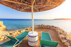 Parasole i dwa pustego deckchairs na brzeg piasku wyrzucać na brzeg Zdjęcie Stock