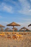 Parasole i pokładów hole w plaży przy zmierzchem Portugal algarve Obrazy Stock