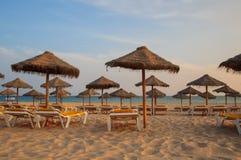 Parasole i pokładów hole w plaży przy zmierzchem Portugal algarve Fotografia Stock
