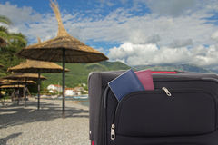 Parasole i walizka z paszportami na plaży Zdjęcia Royalty Free