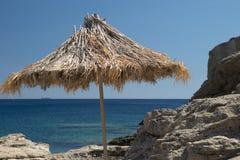 Parasole sulla spiaggia rocciosa greca Fotografia Stock