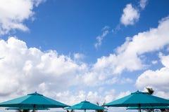 Parasoles azules con el fondo del cielo azul en un día soleado Foto de archivo