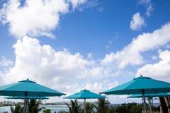 Parasoles azules con el fondo del cielo azul en un día soleado Imagen de archivo libre de regalías