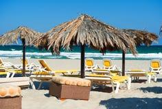 Parasoles con los deckchairs en la playa Imagen de archivo libre de regalías