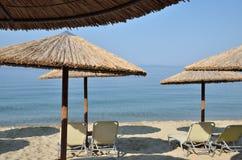 Parasoles de la paja de la playa y pares de sillas Imágenes de archivo libres de regalías