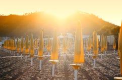 Parasoles de playa en la puesta del sol Foto de archivo libre de regalías