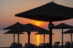 Parasoles de playa en la puesta del sol por el mar imagenes de archivo