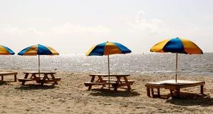 Parasoles de playa multicolores en soporte de madera en la playa Fotografía de archivo
