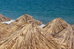 Parasoles de playa por el mar Imagen de archivo libre de regalías