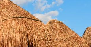 Parasoles del paraguas de la paja/de bambú contra fondo del cielo azul Foto de archivo